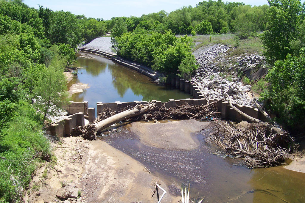 Photo of Berg Oliver Project - Airport Freeway. View of construction site with water, trees, and rubble
