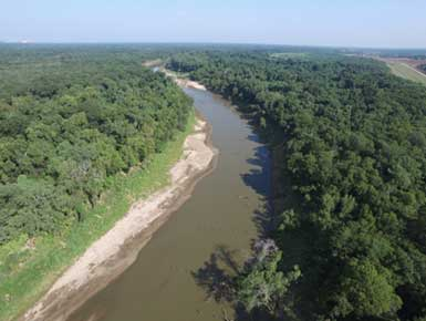 Drone view of river with trees and sand bank on edges