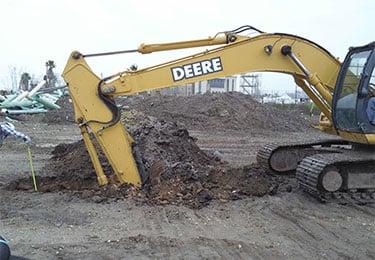 Crane putting scoop into dirt